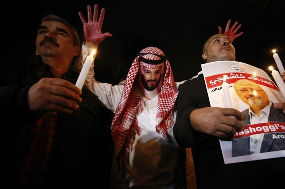 Protester holding up image of Saudi crown prince with bloody hands at a vigil for slain journalist Khashoggi