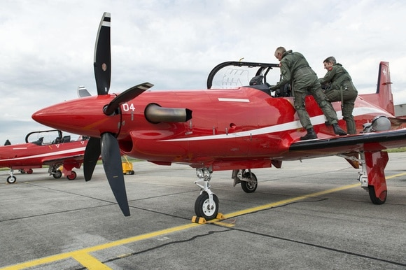Red PC-21 training aircraft with instructor and student