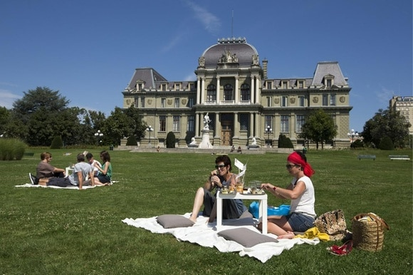 People picnic on the grass. In the background a palatial building.
