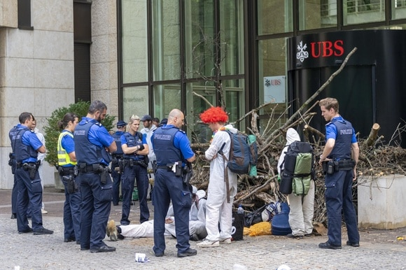 Police checking environmental protesters outside a UBS bank building in Basel