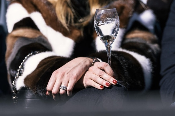 A woman in a fur coat holds a glass of wine