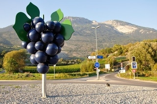 A sculpture of a bunch of grapes on a graveled roundabout