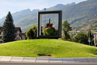 A large frame situated on a mound of grass on a roundabout