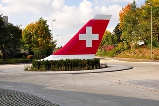 Tail wing of a Swissair aeroplane situated in bushes on a roundabout