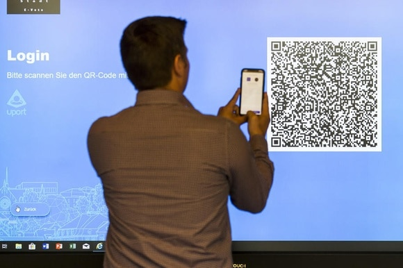 Man with mobile phone taking picture of screen code