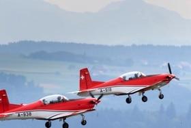 En vuelo, dos pequeños aviones pintados en tojo y blanco