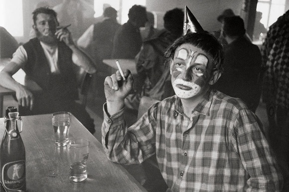 A man sits holding a cigarette with his face painted as a clown.