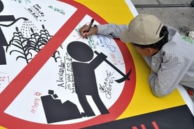 School children of the Canton of Geneva sign a banner against the child labour