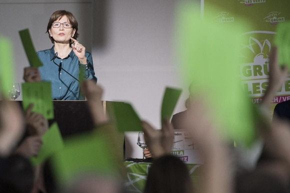 Woman at a lectern and show of hands with green cards