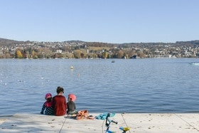 A woman and two young children sit on the waterfront of Lake Zurich