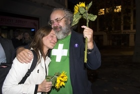 Man in Green t-shirt and woman holding sunflowers