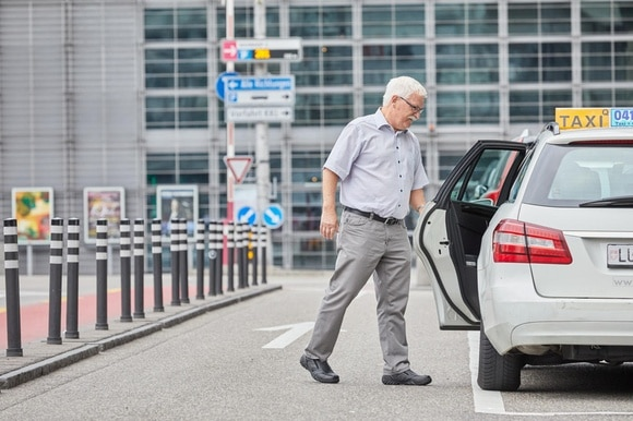Elderly man opening taxi car door