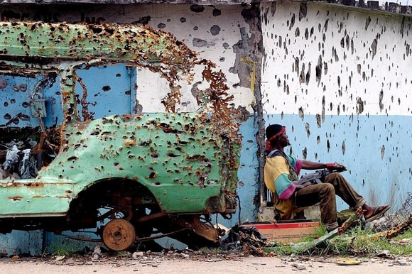 Armed man in Liberia sitting next to a car wreck riddled with bullets