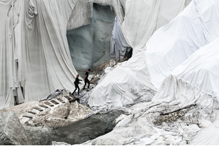 Glaciers draped with cloth, two people walk along the steps.