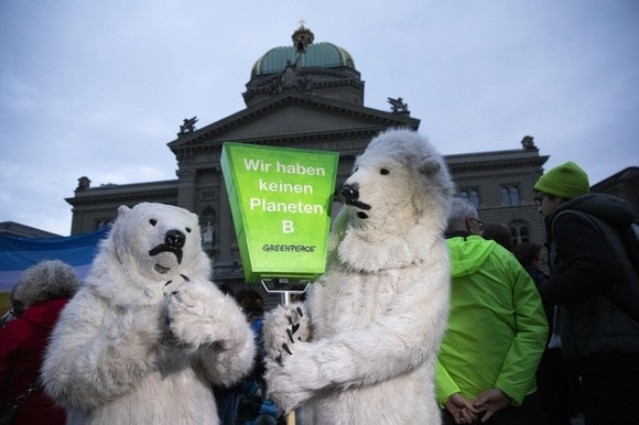 Campaigners in polar bear outfits outside the Federal Palace in Bern