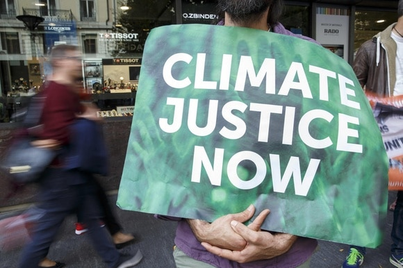 Climate protester holds sign saying Climate Justice Now
