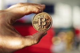 Hand holds a bitcoin