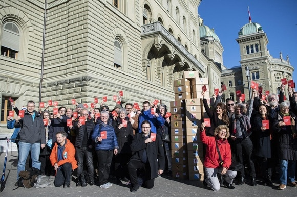 Group of people with red booklet in front of parliament building