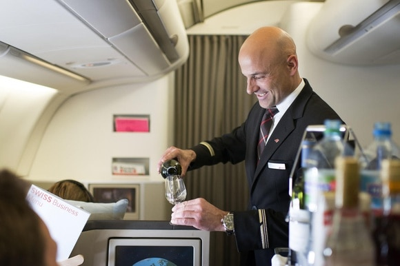 A flight attendant attends to Swiss Business Class passengers
