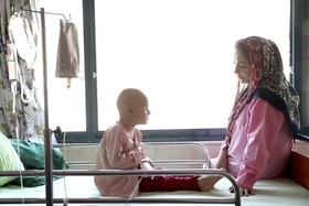 Boy with cancer in hospital with his mother