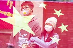 Two masked people behind Chinese flag