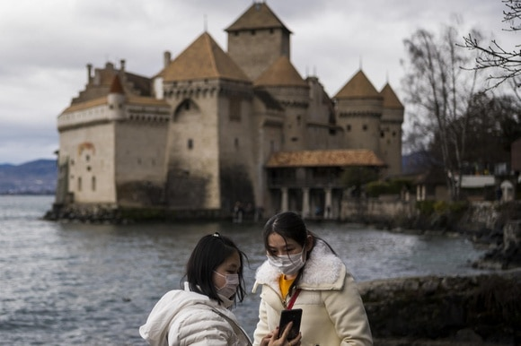 Two masked Chinese women in front of Swiss castle