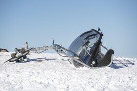 The broken chairlift sits on the snow