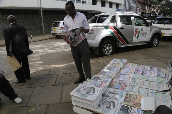 man with stacks of newspapers