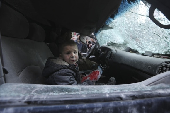 A boy cries, sitting in a destroyed car