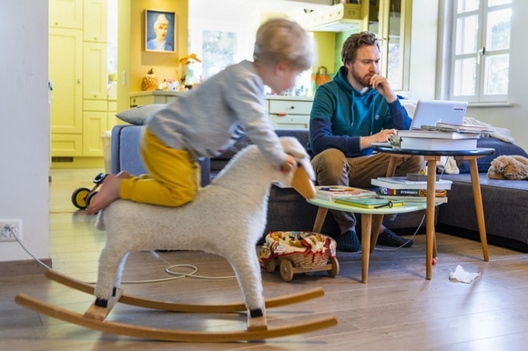 Boy on rocking sheep, father doing home office