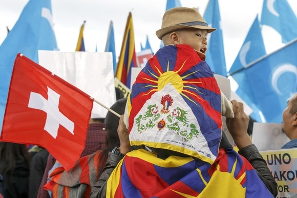 A boy sits on his father s shoulders draped in a Tibetan flag
