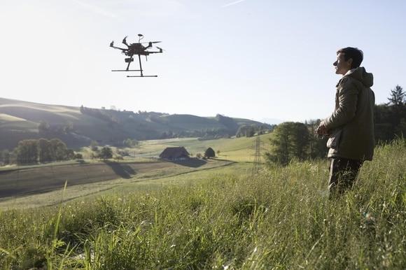 Jovem pilota um drone em uma plantação