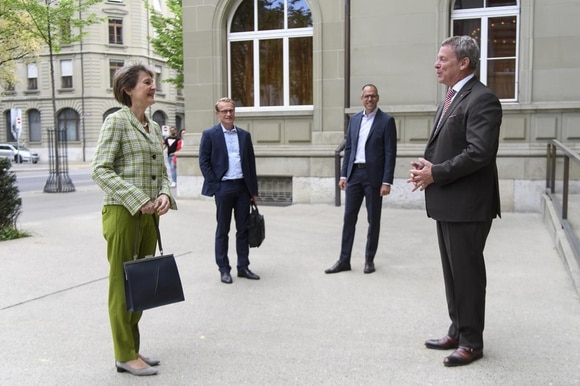 President Sommaruga and three men waiting outside a building
