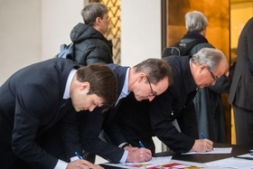 Three men signing documents