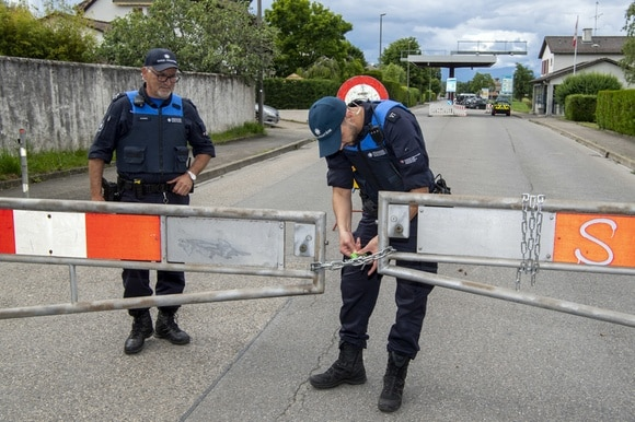 Swiss soldiers inform a cyclist that the Swiss-French border near Thonex, Geneva, is closed