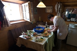 The hut ward assistant prepares salad for the guests in the kitchen of the Saseo mountain hut.