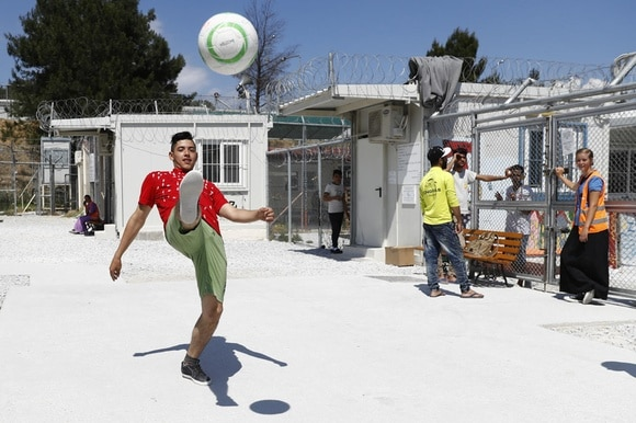 Teenager playing football in a refugee camp