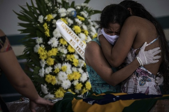 People grieve a Covid-19 victim in the city of Manaos, Brazil