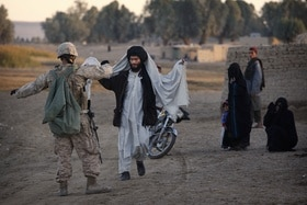 A US marine searches an Afghan man in Helmand Province (2009).