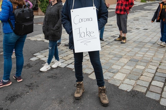 A protester wearing a Corona Fake placard