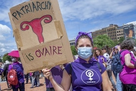 Woman at a demo holding placard