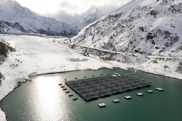 Floating barges with solar panels are pictured on the Lac des Toules