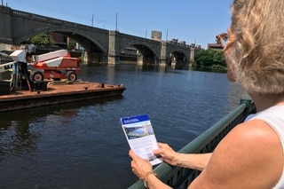 Woman with brochure at riverside