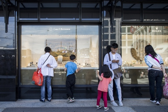 Asian tourists looking in a Swiss watch window