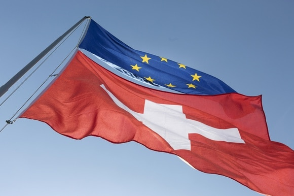 European and Swiss flags flying on a pole