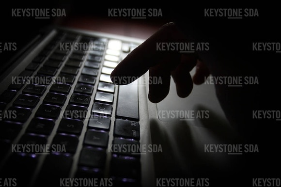 Hand poised over computer keyboard