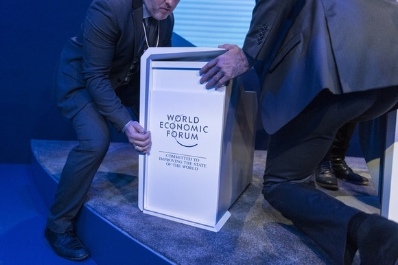 Men moving a podium with WEF motto