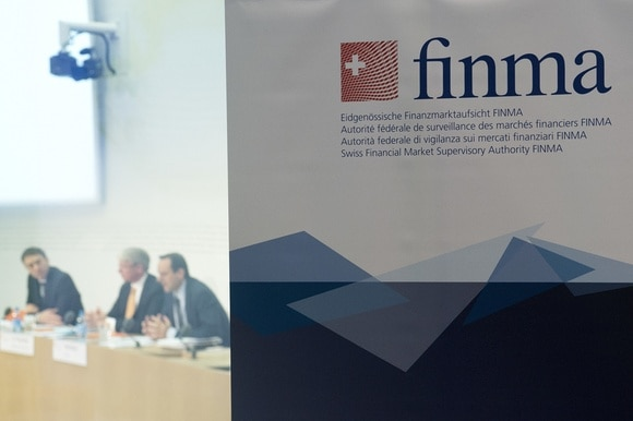 FINMA logo and three men in background