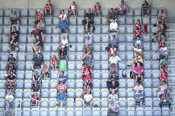 Spectactors at a football match sitting apart