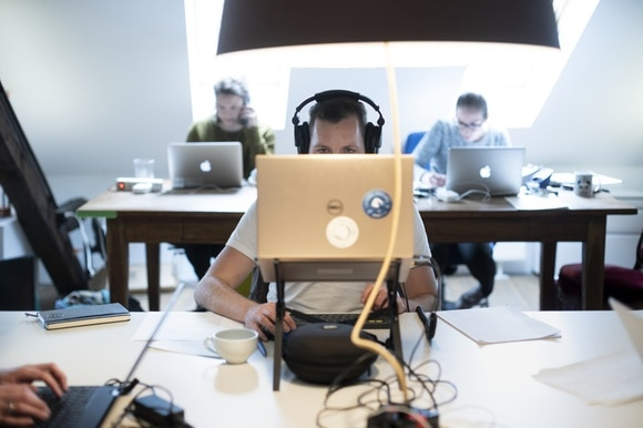 Man sits behind computer, with only eyes and headphones showing